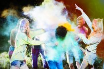 Friends throwing chalk dye on man at music festival — Stock Photo