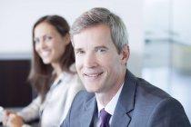 Uomo d'affari sorridente in riunione in ufficio moderno — Foto stock