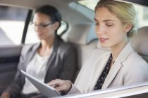 Businesswoman using digital tablet in car back seat — Stock Photo