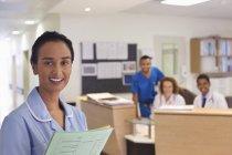 Медсестра улыбается в коридоре современной больницы — стоковое фото