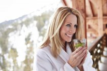 Woman having drink on cabin balcony — Stock Photo