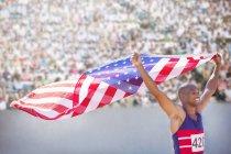 Pista y campo atleta sosteniendo la bandera americana en el estadio - foto de stock