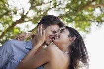 Усміхаючись, пара обіймати під дерево — стокове фото