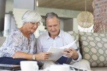 Älteres Ehepaar lesen Papiere zusammen auf sofa — Stockfoto