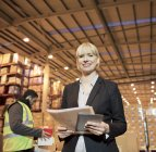 Businesswoman with folder and tablet computer in warehouse — Stock Photo