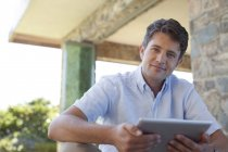 Man using tablet computer on porch — Stock Photo