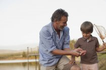 Smiling grandfather and grandson fishing at lakeside — Stock Photo