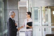 Gens d'affaires se serrant la main dans l'immeuble de bureaux — Photo de stock