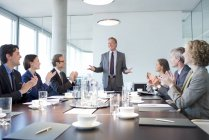 Uomini d'affari applaudono collega in riunione in ufficio moderno — Foto stock