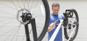 Skillful caucasian man working on bicycle in driveway — Stock Photo