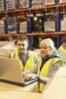Workers using laptop in warehouse — Stock Photo