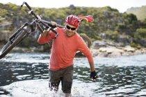 Кавказский взрослый человек, перевозящих горный велосипед в реке — стоковое фото