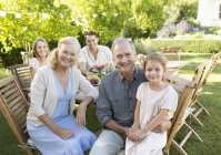 Happy family smiling at table outdoors — Stock Photo