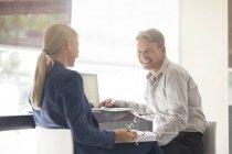 Деловые люди разговаривают за столом в помещении — стоковое фото