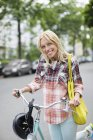 Woman pushing bicycle on city street — Stock Photo