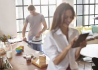 Woman using digital tablet as boyfriend irons in kitchen — Stockfoto