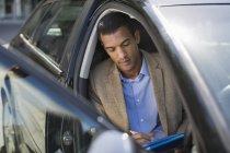 Jovem empresário negro trabalhando no carro — Fotografia de Stock
