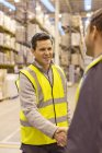 Workers shaking hands in warehouse — Stock Photo