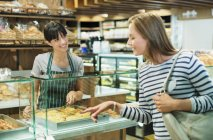 Клерк порції замовника на лічильник гастроному в продуктовому магазині — стокове фото