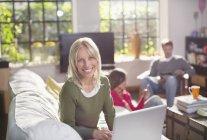 Woman using laptop on sofa — Stock Photo