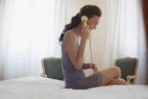 Lächelnde Frau im Nachthemd am Telefon sprechen — Stockfoto