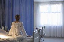 Vue arrière du patient robe portant sur lit d'hôpital — Photo de stock
