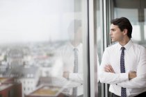Businessman looking at modern office window — Stock Photo