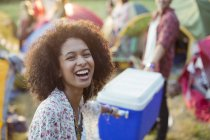 Portrait of laughing woman helping man carry cooler outside tents at music festival — Stock Photo