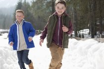 Portrait of happy boys running in snowy lane — Stock Photo