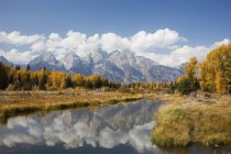 Mountains and landscape reflected in still river — Stock Photo