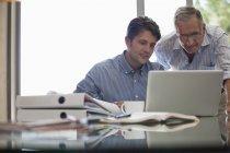 Homme plus âgé et homme plus jeune travaillant ensemble au bureau — Photo de stock