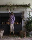 Boy decorating Christmas fireplace — Stock Photo