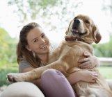 Lächelnde Mädchen umarmt Hund auf sofa — Stockfoto