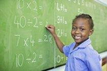 African american student writing on blackboard in class — Stock Photo