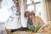 Women using laptop together in bedroom — Stock Photo