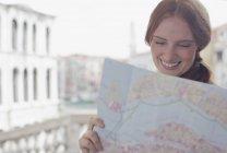 Donna sorridente che osserva giù mappa — Foto stock