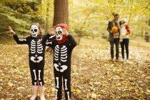 Kinder im Skelett Kostüme zu Fuß im park — Stockfoto