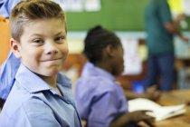 Allievo maschio caucasico sorridente in classe — Foto stock
