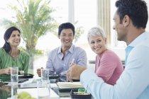 Uomini d'affari sorridenti a pranzo all'ufficio moderno — Foto stock