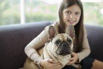 Девочка расслабляющая собака на диване в современном доме — стоковое фото