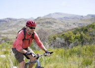 Smiling mountain biker in rural landscape — Stock Photo