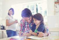 Father helping daughter use coloring book — Stock Photo
