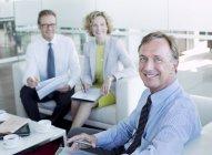 Empresários sorrindo no lobby do escritório moderno — Fotografia de Stock