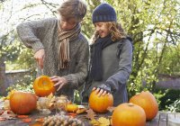 Children carving pumpkins together on outdoor table — Stock Photo