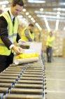 Empresario comprobando paquetes en cinta transportadora en almacén - foto de stock