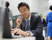 Empresário, sentado à mesa a falar no fone de ouvido — Fotografia de Stock