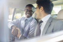 Smiling businessmen shaking hands in car — Stock Photo