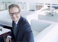 Homme d'affaires souriant dans le hall au bureau moderne — Photo de stock