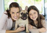 Улыбающиеся мать и дочь обнимают собаку — стоковое фото