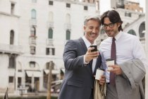 Smiling businessmen with coffee looking down at cell phone in Venice — Stock Photo
